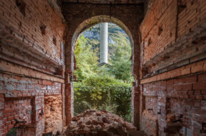 terracotta brick walls and arched window, industrial ruins, belluno, veneto, italy