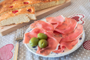 homemade Apulian focaccia served with Parma's ham and olives, typical Italian food