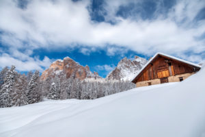 abandoned buildings of Fedarola hut, in the background the Tofana di Rozes, winter landscape in the Dolomites, Cortina d'Ampezzo, Belluno, Veneto, Italy