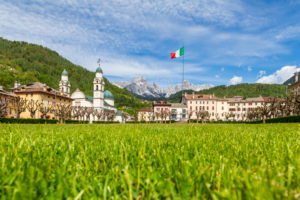 the center of Agordo with the church with two bell towers and the large green lawn called 'broi', agordino, belluno, veneto, italy