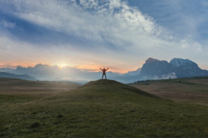 hiker standing in silhouette at dawn on the meadows of the alpe di siusi, in the background the Sassolungo  / Langkofel, Dolomites, Kastelruth, South Tyrol, Italy
