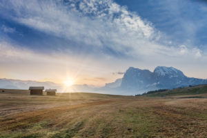 Rising sun in front of Sassolungo / Langkofel and the Sassopiatto / Plattkofel on the Alpe di Siusi / Seiser Alm meadows, Dolomites, Kastelruth, South Tyrol, Italy and on the Alpe di Siusi meadows,