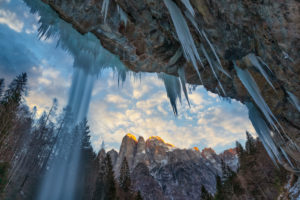 San Lucano valley in Agordino, the waterfall 'dell'Inferno' in winter with the Agner mountain at sunset, Dolomites, Taibon, Belluno, Italy