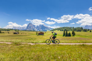 cyclist with an electric mountain bike (e-bike) pedaling in Alpe di Siusi, Seiseralm, South Tyrol, Dolomites, Italy