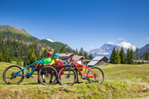 man and woman sitting on a bench in face of Civetta mountain near Cherz alm, tour with e-bike in the natural landscape of Dolomites, livinallongo del col di lana, belluno, veneto, italy