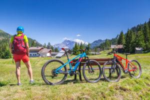 woman standing in face of Civetta mountain near Cherz alm, tour with e-bike in the natural landscape of Dolomites, livinallongo del col di lana, belluno, veneto, italy