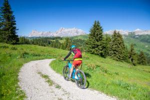 woman with e-bike in the natural landscape of mount cherz, dolomites, livinallongo del col di lana, belluno, veneto, italy
