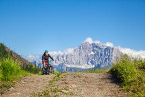 woman pedaling on a gravel road, in the background  the Civetta mountain near Cherz alm, tour with e-bike in the natural landscape of Dolomites, livinallongo del col di lana, belluno, veneto, italy