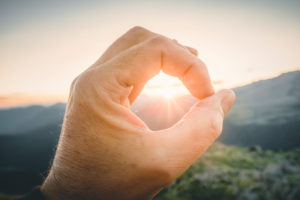 Man hand circling the sun with with fingers at sunrise