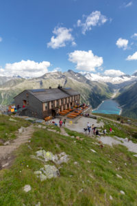 Hikers at Olperer refuge with Lake Schlegeispeicher on the background, Zillertal Alps, Tyrol, Schwaz district, Austria