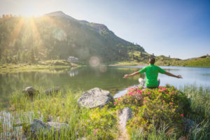 man 40 - 50 years old in relaxing position at sunrise on the shore of the Colbricon alpine lake in summer with rhododendron flowering and mountain reflected on the water, Lagorai, Trentino, Italy, Europe