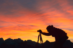 Silhouette of photographer taking pictures in mountain at sunset, Dolomites