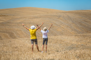 mom and daughter with arms raised to the sky in val d'orcia, summer scene, Castiglione d'Orcia, province of Siena, Tuscany, Italy