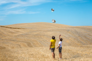 mother and daughter play with their hats in a field in Val d'Orcia, Castiglione d'Orcia, province of Siena, Tuscany, Italy
