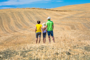 family, father, mother and young daughter from behind look at the hills in Val d'Orcia, Castiglione d'Orcia, province of Siena, Tuscany, Italy