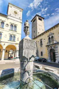 Italy, Veneto, Belluno, Dolomites, the statue of St. Gioatà on the fountain in Piazza del Duomo between the Palazzo dei Rettori with the clock tower and Palazzo dei Vescovi