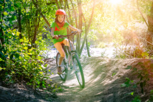 Italy, Veneto, Belluno, Agordino, little girl ( 10 years old) has fun with her bicycle along a forest path