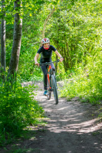Italy, Veneto, Belluno, Agordino, woman cyclist (45 years old) with an e-bike on a dirt road in the woods