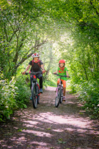 Italy, Veneto, Belluno, Agordino, smiling mom and daughter ride a bicycle down a road among the trees