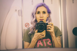 violet hair girl taking a selfie in the mirror of the bathroom on an airplane