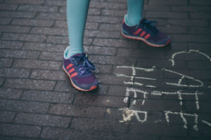 legs of a little girl stepping on some bricks floor with colorful sneakers
