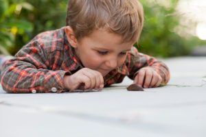 Junge spielt am Boden mit einer Nacktschnecke