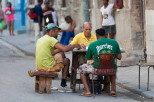 Caribbean, Cuba, Havana, three men playing at dominoes, roadside