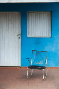 Caribbean, Cuba, Valle de Viñales, Viñales, rocking chair in front of blue house wall and white door