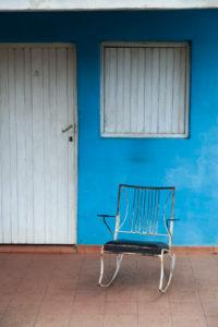 Karibik, Kuba, Cuba, Valle de Viñales, Viñales, Schaukelstuhl vor blauer Hauswand und weißer Tür