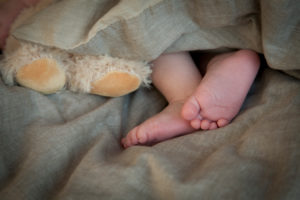 Newborn, baby, bare baby feet in bed next to teddy feet