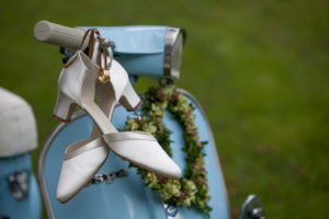 Rings and bridal shoes hang on the handlebar of a light blue Vespa
