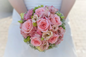Bride holds pink bridal bouquet in hands, close up