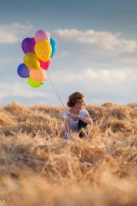 Junge Frau mit bunten Luftballons im  gemähten Getreidefeld