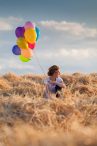 Young woman with colorful air balloons in a mowed grain field