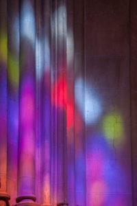 buntes Lichtspiel von Glasfenster auf Kirchensäulen, Andalusien, Spanien, Carmona, Iglesia Prioral de Santa Maria,
