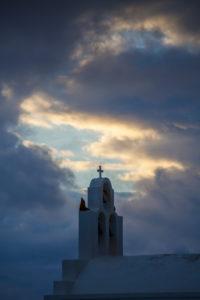 Wolkendurchbruch mit Abendlicht vor dem Kreuz einer Kapelle, Thira, Griechenland, Santorini, Santorin