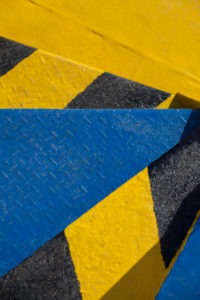 knallbunte Metalltreppenstufen auf einer Fähre, Farbkontrast gelb blau schwarz, Blick treppabwärts