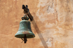 Glocke vor ockerfarbener Hauswand, Griechenland, Kreta, Insel Spinalonga, Kalydon