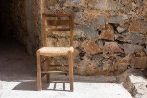 brauner Holzstuhl mit geflochtenem Sitz vor Steinmauer auf der Leprainsel Spinalonga, Griechenland, Kreta, Kalydon