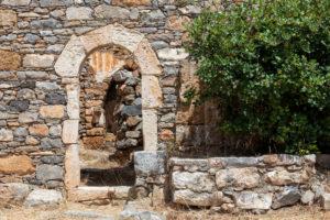 Blick auf Torbogen eines zerfallenen Hauses auf der Leprainsel Spinalonga, Griechenland, Kreta, Kalydon