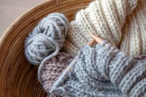 Strickzeug mit flauschiger Wolle und dicken Nadeln in Korb, Erdtöne