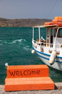 Boot im Hafen von Elounda. Davor orange Treppe mit Aufschrift Welcome, Griechenland, Insel Kreta, Kalydon
