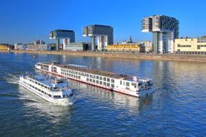 Ausflugsschiff und Flusskreuzfahrtschiff auf dem Rhein vor den Kranhäusern im Rheinauhafen, Köln, Nordrhein-Westfalen, Westdeutschland, Deutschland
