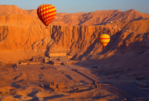 Hot-air balloons above the temple of Hatshepsut under early morning sun in Thebes-West, Luxor, Upper Egypt, Egypt