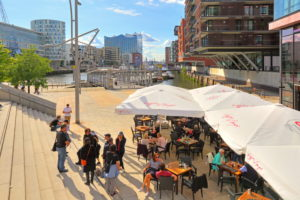 Magellan terraces with street cafe at the Sandtorhafen and Elbphilharmonie on the Elbe island Grasbrook in the Hafencity at the harbor, Hamburg, Hamburg State, Germany