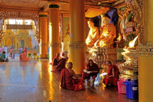 Monks in front of one of the altars in the temples of Shwedagon Pagoda, Yangon, Myanmar