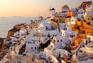Village view on the slope of the cliff coast with windmills, Ia, (Oia), Santorin, (Thira), Cyclades, Aegean Islands, Aegean Sea, Greece, evening sun