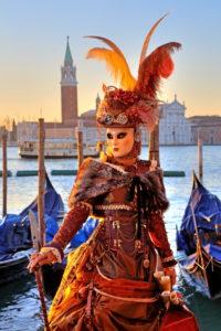 Fantasiemaske an der Wasserfront mit Insel San Giorgio beim Karneval, Venedig, Venetien, Italien