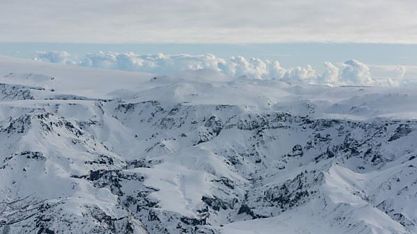 Isländische schneebedeckte Landschaft aus der Vogelperspektive, Vulkanberge und im Hintergrund der Atlantik