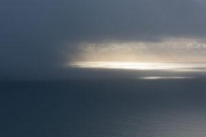 Wolkenbruch über dem Atlantischen Ozean, südlich von Island, fotografiert aus einer Cessna im Februar.